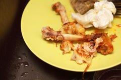 有骨头的肮脏的板材在晚餐以后。食物残羹剩饭 免版税库存照片