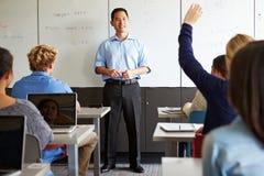 有高中学生的家庭教师使用膝上型计算机的类的 库存图片