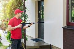 有高压洗衣机清洁房子门面的工作者 免版税库存图片