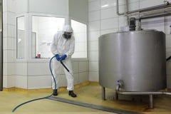有高压洗衣机清洁地板的工作者 免版税图库摄影