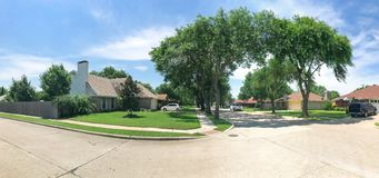 有高大的树木机盖、路和单身家庭的房子的相当全景邻里 免版税库存照片