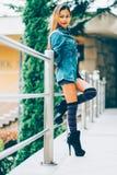 有高小山和长的条纹膝盖袜子的时兴的少妇佩带的蓝色牛仔裤夹克 秋天时尚样式 库存图片