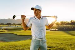 有高尔夫俱乐部的男性高尔夫球运动员在路线 免版税库存图片