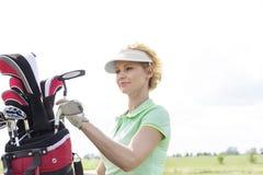 有高尔夫俱乐部袋子的女性高尔夫球运动员反对清楚的天空 免版税库存图片