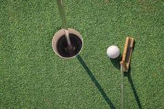 有高尔夫球和孔的轻击棒 免版税图库摄影