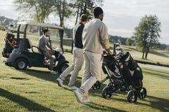 有高尔夫球袋的一起花费时间的高尔夫球运动员和高尔夫车 图库摄影