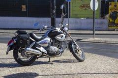 有高度优美的镀铬物零件的一辆现代哈利戴维森马达自行车在一条被修补的街道上停放了在Albuderia在葡萄牙 免版税库存图片