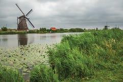 有高灌木和风车的平直的运河在银行在小孩堤防的一多云天 库存照片