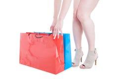 有高跟鞋和色的购物袋的妇女腿 免版税库存照片