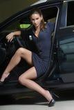 有高跟鞋的妇女穿上鞋子从汽车出来 免版税库存图片