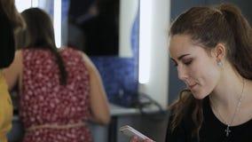 有高马尾辫的英俊的妇女在手机聊天在化装室 股票录像