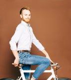 有髭和胡子的一个年轻人坐一辆时兴的现代fixgear自行车 牛仔裤和衬衣,蝶形领结行家样式 免版税图库摄影