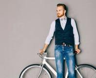 有髭和胡子的一个年轻人是在时兴的现代fixgear自行车附近 牛仔裤和衬衣、背心和蝶形领结行家styl 图库摄影