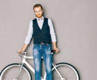 有髭和胡子的一个年轻人是在时兴的现代fixgear自行车附近 牛仔裤和衬衣、背心和蝶形领结行家styl 免版税图库摄影