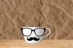 有髭的杯在褐色的桌上 免版税图库摄影