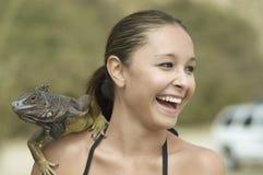 有鬣鳞蜥的笑的妇女在肩膀 免版税库存图片