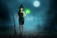 有魔法咒语和飞行笤帚的秀丽亚裔巫婆妇女 免版税库存图片