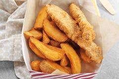 有鲜美油煎的炸鱼加炸土豆片的纸箱在桌上 库存照片