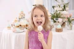 有鲜美蛋糕流行音乐的逗人喜爱的小女孩 免版税库存照片