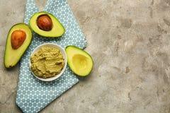 有鲜美鳄梨调味酱捣碎的鳄梨酱和成熟鲕梨的板材在桌上 免版税库存照片