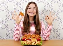 有鲜美鸡块和ok手标志的十几岁的女孩 免版税库存照片