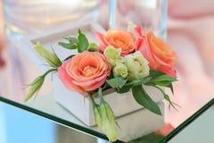 有鲜花的白色木箱在一张被反映的桌上站立 图库摄影