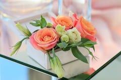 有鲜花的白色木箱在一张被反映的桌上站立 免版税库存图片