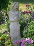 有鸟的夫人在庭院里 库存照片