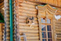 有鸟的椋鸟科房子在一个木大厦的墙壁上 免版税图库摄影
