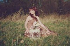 有鸟笼的女孩 免版税库存图片