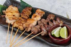 有鸡和内脏的特写镜头Yakitori日本式烤鸡串服务与被切的石灰 图库摄影