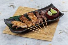有鸡和内脏的Yakitori日本式烤鸡串服务与在黑石板材的被切的石灰 免版税库存照片