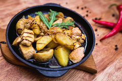 有鸡和土豆的热的分配的平底锅 图库摄影