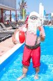 有鸡尾酒和海滩球的地道圣诞老人 免版税图库摄影
