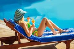 有鸡尾酒杯的少妇在轻便折叠躺椅的游泳池附近 免版税库存图片