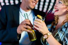 有鸡尾酒的人们在酒吧或俱乐部 免版税库存图片