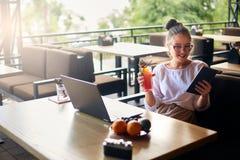 有鸡尾酒的微笑的混合的族种妇女在手中与膝上型计算机一起使用 玻璃饮料汁液的女实业家身体的 图库摄影