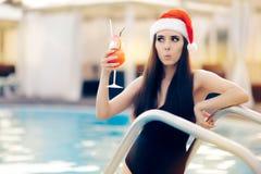 有鸡尾酒的惊奇的圣诞节妇女在水池 免版税库存图片