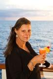 有鸡尾酒的愉快的妇女在游轮 免版税图库摄影