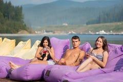 有鸡尾酒的朋友在游泳池附近的被缓冲的懒人在河背景  免版税库存照片