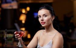 有鸡尾酒的迷人的妇女在夜总会或酒吧 图库摄影