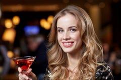 有鸡尾酒的迷人的妇女在夜总会或酒吧 库存图片
