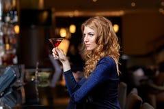 有鸡尾酒的迷人的妇女在夜总会或酒吧 库存照片