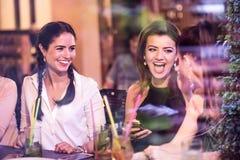 有鸡尾酒的年轻美丽的妇女在酒吧或俱乐部 免版税库存照片
