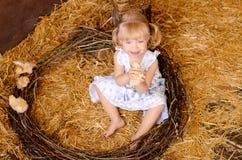 有鸡的白肤金发的女孩 免版税图库摄影