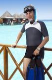 有鸭脚板、面具和管的年轻体育人在一个房子的sundeck在海的 马尔代夫 库存照片