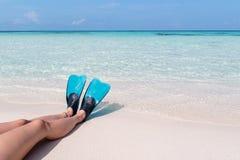有鸭脚板的妇女腿在一个白色海滩在马尔代夫 作为背景的透明的大海 库存图片