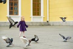 有鸽子的女孩在街道上 免版税库存图片