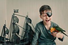 有鹦鹉和风船的男孩海盗 免版税库存照片