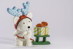 有鹿角、爬犁和礼物的白熊小雕象 库存图片